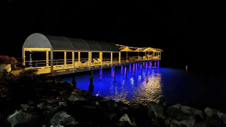 Airlie Beach, Queensland, Australia - April 2021: Pier over ocean lit up at night for use of guests at luxury resort hotel