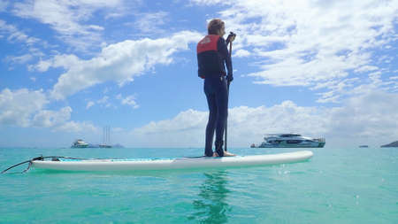 Whitehaven Beach, Whitsundays, Queensland, Australia - April 2021: Slim young woman in stinger suit standing on a surfboard paddle board with tourist boats background Редакционное