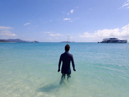 Whitehaven Beach, Whitsundays, Queensland, Australia - April 2021: Man enters clear turquoise water and white silica sand with tourist cruise boats in background Редакционное