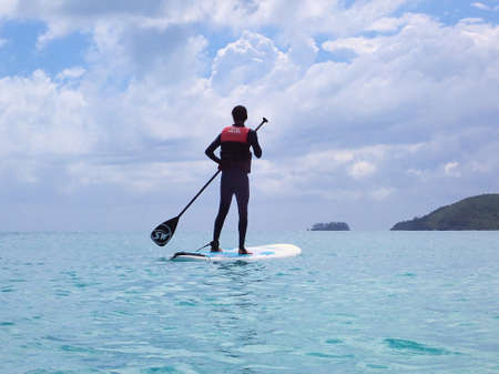 Whitehaven Beach, Whitsundays, Queensland, Australia - April 2021: Male in stinger suit standing on a surfboard paddle board with island background
