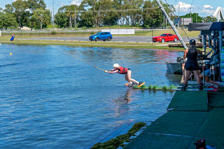 Mackay, Queensland, Australia - April 2021: A young girl learning to wakeboard at a cable ski park