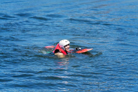 Mackay, Queensland, Australia - April 2021: Male learning to wakeboard at a cable ski park has fallen off and swimming to shore Редакционное