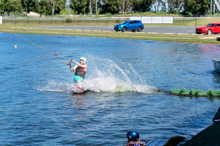Mackay, Queensland, Australia - April 2021: Man learning to wakeboard at a cable ski park