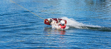 Mackay, Queensland, Australia - April 2021: Man learning to wakeboard at a cable ski park and falling off as the rope p