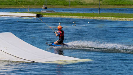 Mackay, Queensland, Australia - April 2021: A young girl wearing a safety helmet and life jacket enjoying a ride on a knee board at a cable park