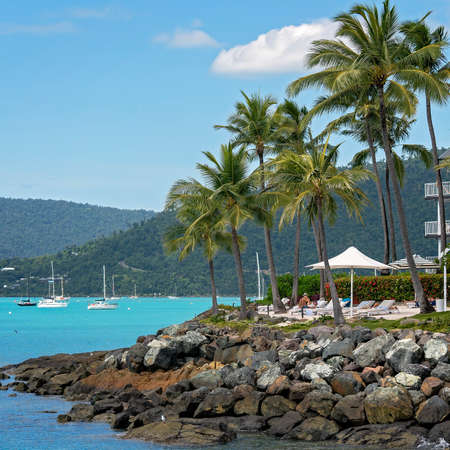 Airlie Beach, Queensland, Australia - April 2021: Holidaymakers relaxing at oceanfront hotel resort with rocky shore and yachts at anchor