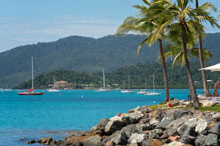Airlie Beach, Queensland, Australia - April 2021: The rocky foreshore in front of a luxury tourist hotel with yachts anchored in the bay Редакционное