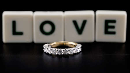 A diamond eternity ring, also known as an infinity ring, symbolizing never ending love, on black background with letters LOVE