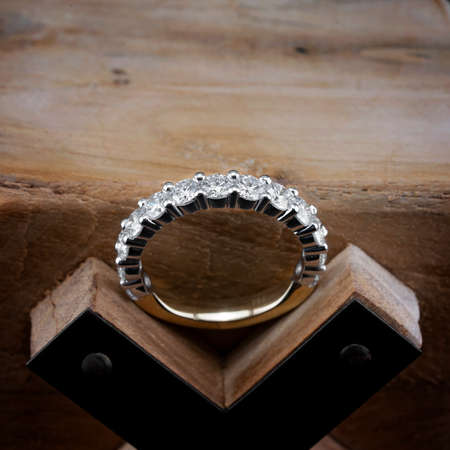 A diamond eternity ring, also known as an infinity ring, symbolizing never ending love, sitting on a wooden letter X