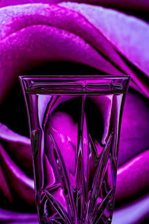 Refraction of a background closeup of a pink rose reflected in the etched crystal foreground glass Banco de Imagens