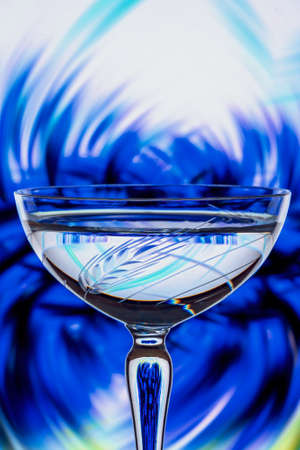 Refraction of a blue flower background closeup reflected in the etched crystal foreground glass Banco de Imagens