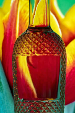 Light refraction caused by light traveling through glass filled with water and reflecting its colorful background. Banco de Imagens