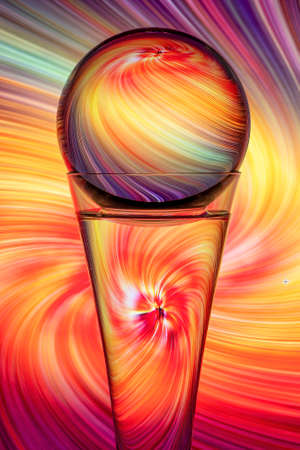Light refraction caused by light traveling through a round glass globe atop a glass filled with water and reflecting it's colorful swirling background.
