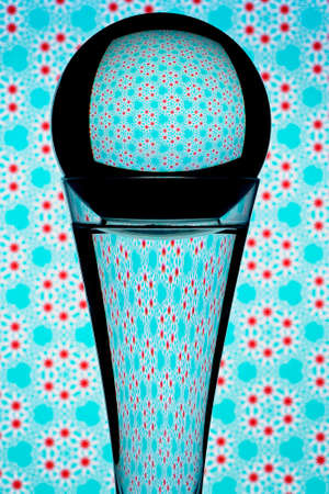 Refraction caused by light traveling through a round glass globe atop a glass filled with water and reflecting it's colorful pattern background.