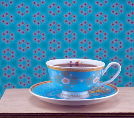 A cup of tea in a floral cup against a blue patterned background