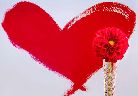 A hand painted red heart background with a dahlia flower in a crystal vase