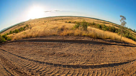 Late evening light on the curved country horizon with dirt road frontage, photographed with a fisheye lens Banco de Imagens