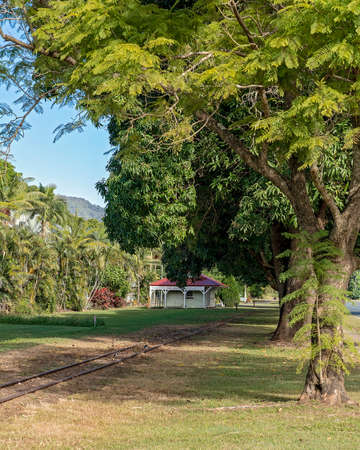 A vintage railway train station at the end of the line nestled amongst a row of mango trees