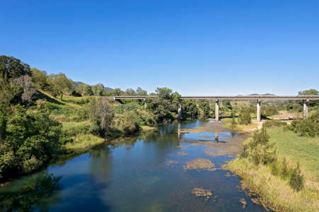 Aerial landscape of a bridge across a rural creek with banks covered in bushland.