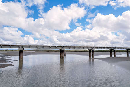 Drone aerial approaching a railway bridge over a local creek under a cloudy blue sky. St Lawrence, Queensland, Austral Standard-Bild