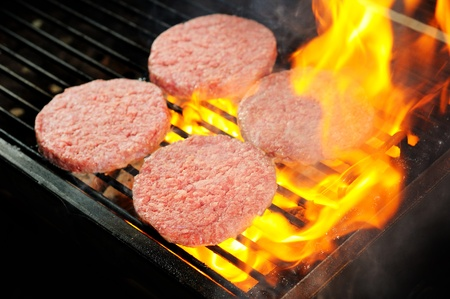 raw Beef burgers being cooked  photo