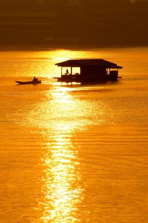 Sunset and boat with floating house at Sangklaburi Kanchanaburi Thailand