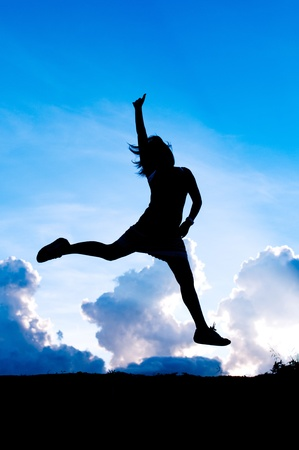 girl silhouette jumping in bllue sky Stock Photo