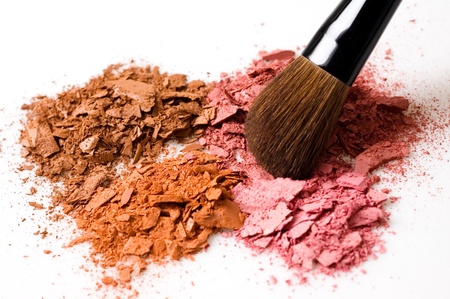 Closeup of crushed blush on white background and cosmetic brush