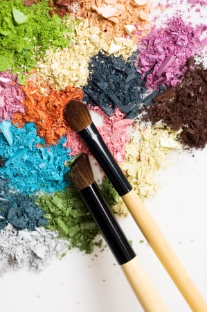 Closeup of blush and multicolor crushed eyeshadows on white background