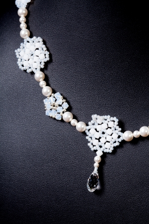 luxury jewellery pearl set necklace over black background photo