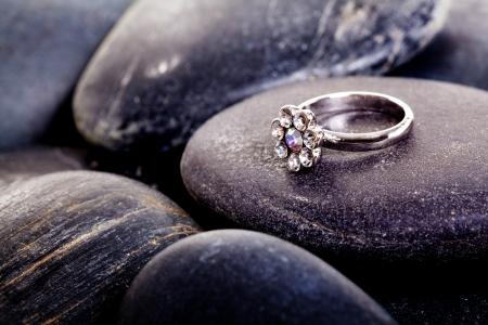 Big diamond ring on a stone, black nature stone, strong love Standard-Bild