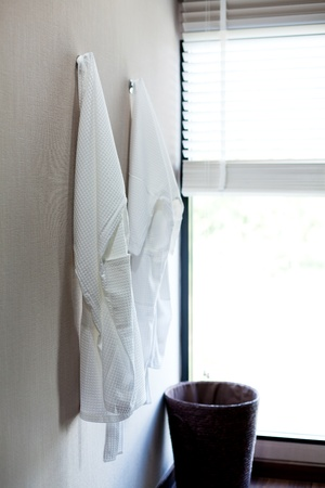 two white bathrobes in bedroom