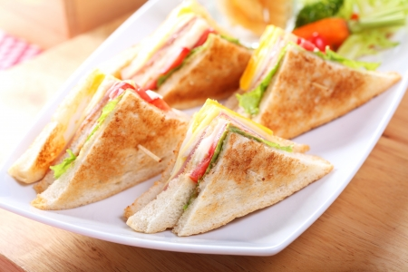 Sandwich with bacon and vegetables on white dish Standard-Bild