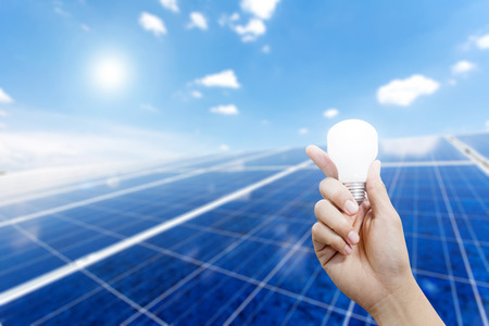 silicium: Solar energy panels and Light bulb in hand, Green energy concept Stock Photo