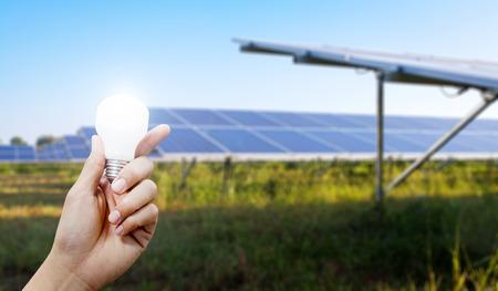 Solar energy panels and Light bulb in hand, Green energy concept Standard-Bild