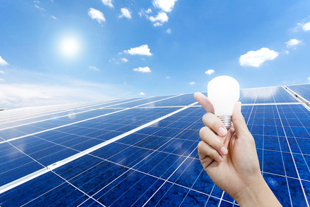 Solar energy panels and Light bulb in hand, Green energy concept Stock Photo
