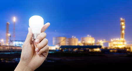 gas plant: Light energy for industry, Hand holding light bulb in industrial topic