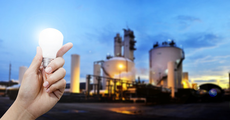 Light energy for industry, Hand holding light bulb in industrial topic