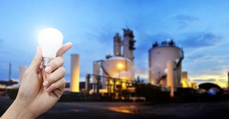 energy work: Light energy for industry, Hand holding light bulb in industrial topic