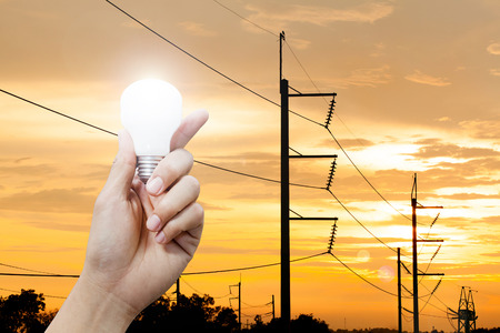Hand holding a glowing light bulb and electricity pole sunset background, power energy