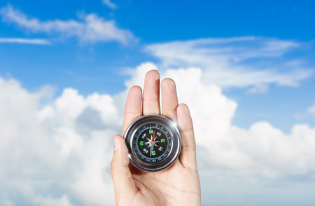 magnetic north: The hand of a man holding a magnetic compass over a blue sky Stock Photo