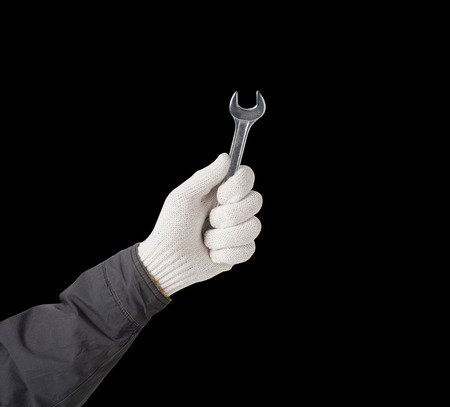 handtool: Working hand in glove holding wrench on a black background Stock Photo