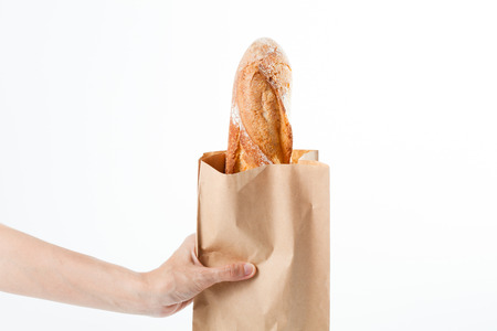 cereals holding hands: Fresh French baquette in brown paper bag Stock Photo
