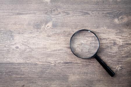 木製テーブルの上の虫眼鏡