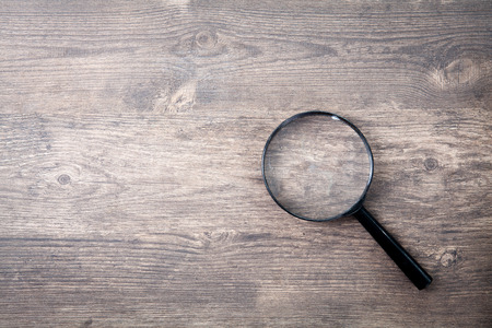 Magnifying glass on wood table