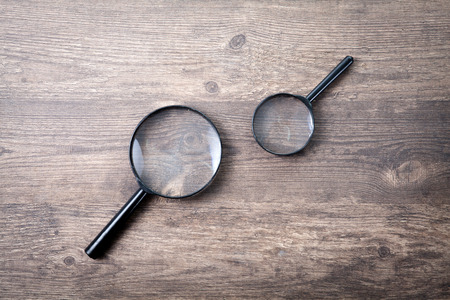 magnifying glass icon: Magnifying glass on wood background Search symbol