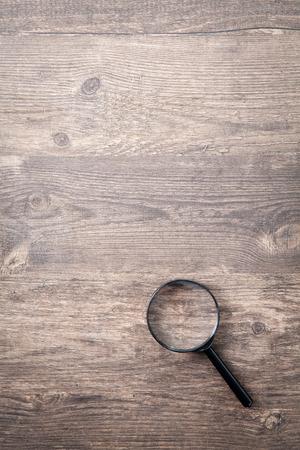 Magnifying glass on wood background Standard-Bild
