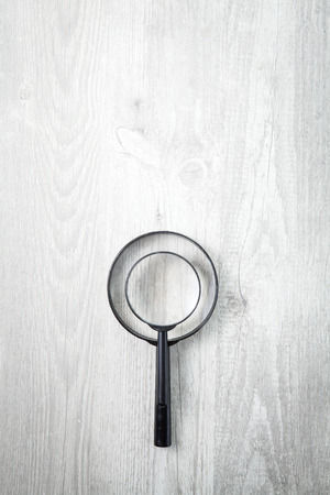wood table: Magnifying glass on wood table