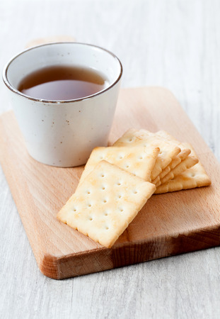 tea and biscuits: Stack of square crackers on wooden table
