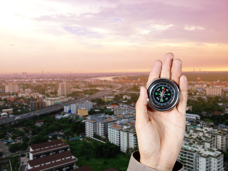 city  buildings: Business direction, The hand of a man holding a magnetic compass over a city buildings Stock Photo